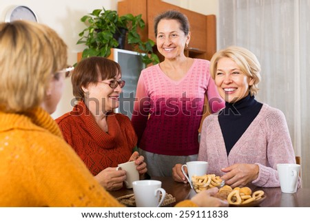 Happy senior female friends drinking coffee and talking