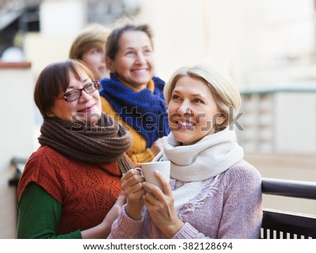 Happy senior female in warm clothes having cup of hot tea on terrace. Focus on blonde woman - stock photo