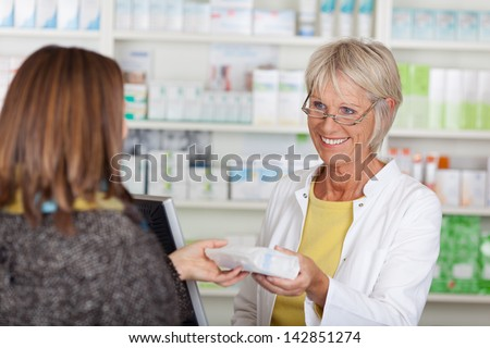 Happy senior female pharmacist giving prescribed medicine to customer in pharmacy - stock photo