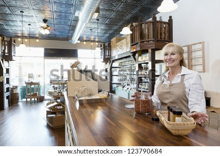 Happy senior female spice merchant standing at counter while looking away in store - stock photo