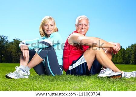 Happy senior fitness couple in the park. - stock photo