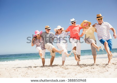 Happy senior friends dancing on the beach