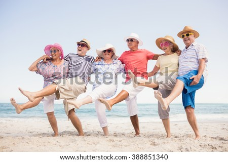 Happy senior friends dancing on the beach - stock photo