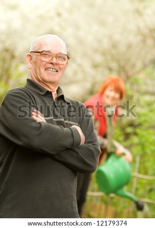 Happy senior gardener and woman watering plants on a background - stock photo
