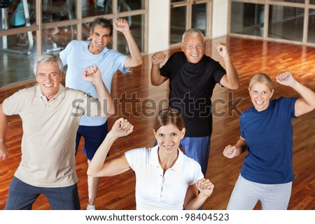 Happy senior group moving and dancing in fitness center