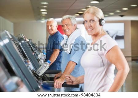 Happy senior group running on treadmills in gym - stock photo