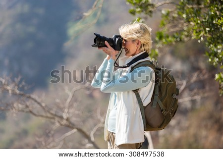 happy senior hiker taking photos with digital camera - stock photo