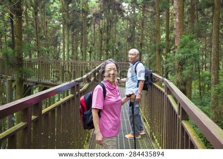 happy senior hiking in the forest park - stock photo