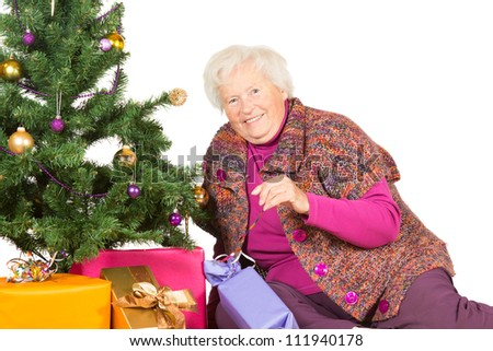 Happy senior lady and grandmother preparing for a family Christmas sitting decorating the Christmas tree and giftwrapped festive gifts - stock photo