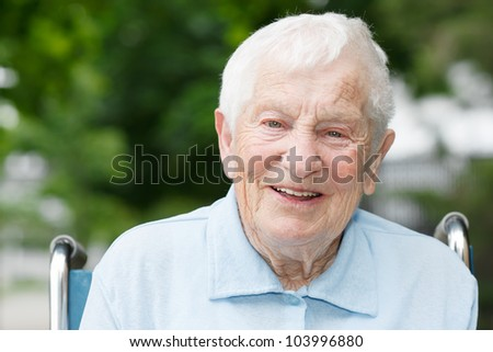 Happy senior lady in wheelchair smiling outside - stock photo