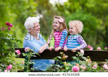Happy senior lady playing with little boy and girl in blooming rose garden. Grandmother with grand children sitting on a bench in summer park with beautiful flowers. Kids gardening with grandparent. - stock photo