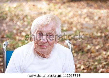 Happy senior lady smiling outside in autumn - stock photo