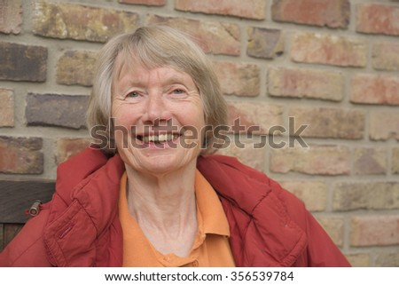 Happy senior lady with a lovely warm beaming smile standing outdoors in front of a brick wall looking at the camera, head and shoulders portrait - stock photo