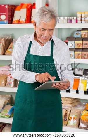 Happy senior male owner using digital tablet in supermarket
