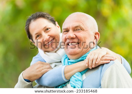 Happy senior man and mature woman in sweaters at autumn park