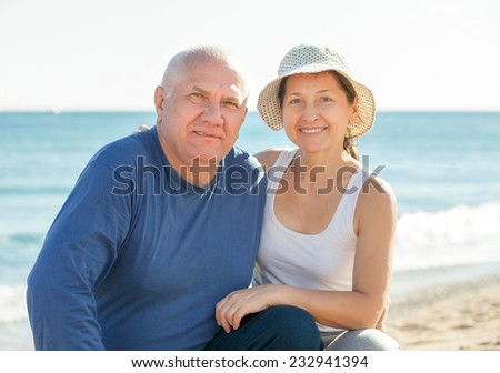 Happy senior man and mature woman together against sea in summer - stock photo
