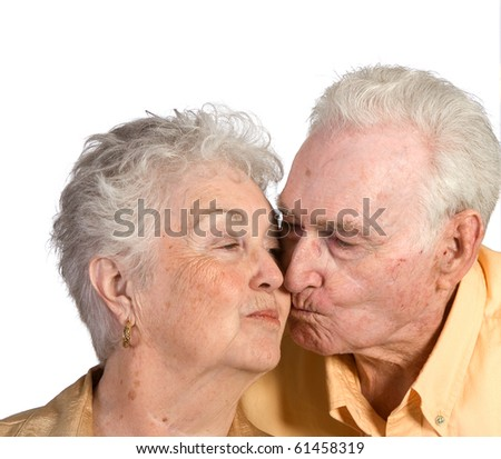 Happy senior man and woman couple kissing. Shot against a white background. - stock photo