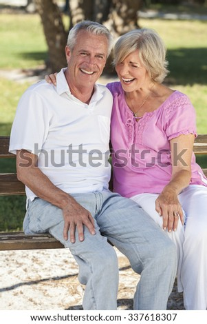 Happy senior man and woman couple sitting laughing together on a park bench outside in sunshine