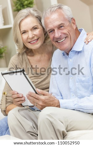 Happy senior man and woman couple sitting together at home smiling and happy using a tablet computer - stock photo