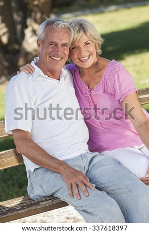 Happy senior man and woman couple sitting together laughing on a park bench outside in sunshine