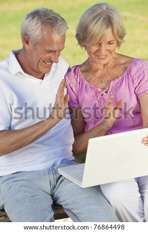 Happy senior man and woman couple sitting together outside in sunshine waving while using a computer for a VOIP internet telephone call - stock photo