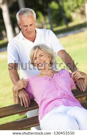 Happy senior man and woman couple smiling and laughing having fun together outside in sunshine - stock photo