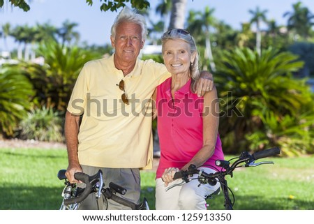 Happy senior man and woman couple together cycling on bicycles in a sunny green park - stock photo