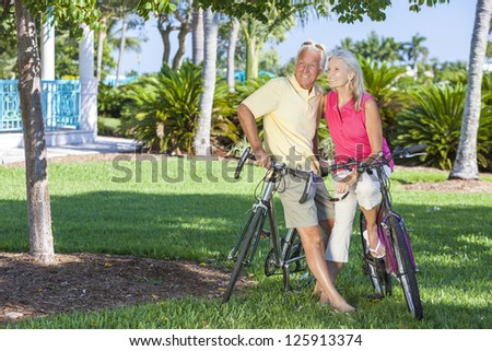 Happy senior man and woman couple together cycling on bicycles in a sunny green tropical park - stock photo