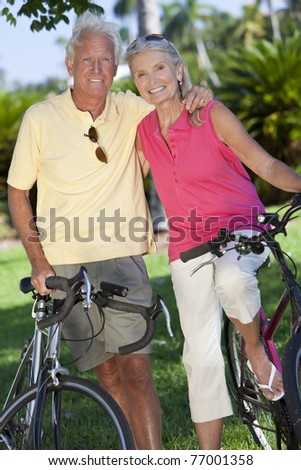 Happy senior man and woman couple together cycling on bicycles outside in a sunny green park