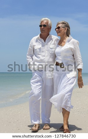 Happy senior man and woman couple together looking out to sea on a deserted tropical beach with bright clear blue sky. - stock photo