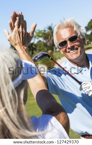 Happy senior man and woman couple together playing golf and celebrating a good shot on the course - stock photo