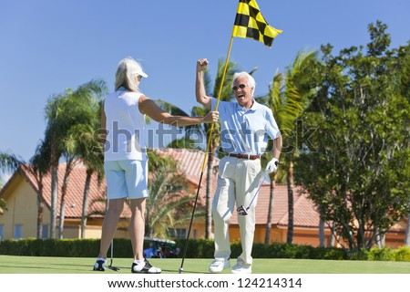 Happy senior man and woman couple together playing golf celebrating on a putting green together - stock photo