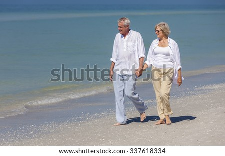 Happy senior man and woman couple walking and holding hands on a deserted tropical beach  - stock photo