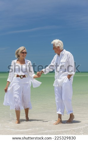 Happy senior man and woman couple walking, laughing and holding hands on a deserted tropical beach with bright clear blue sky - stock photo