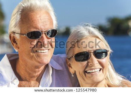 Happy senior man and woman romantic couple together looking out to tropical sea or river wearing sunglasses - stock photo