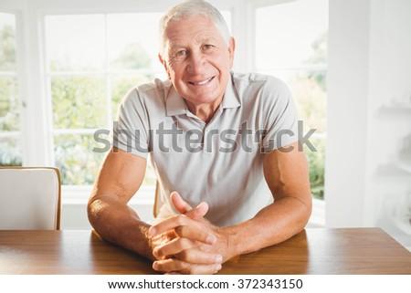Happy senior man crossing fingers at home - stock photo