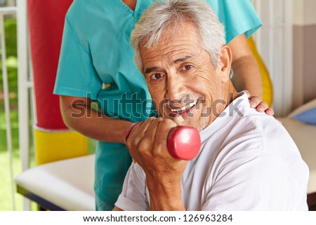 Happy senior man doing dumbbell training at physiotherapy - stock photo
