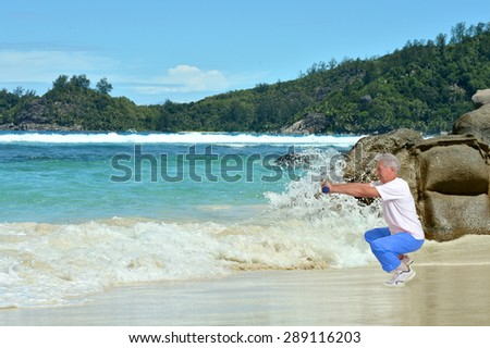 Happy Senior man exercising in summer on  seashore