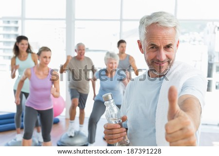 Happy senior man gesturing thumbs up with people exercising in the background at fitness studio - stock photo