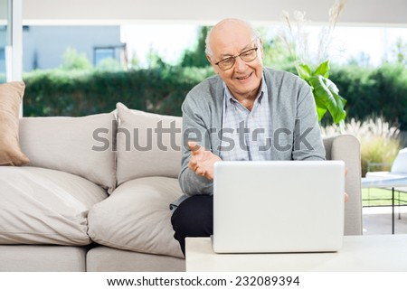 Happy senior man gesturing while video chatting on laptop at nursing home porch - stock photo