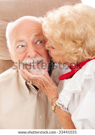 Happy senior man gets a kiss from his sweetie.