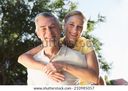 Happy senior man giving his partner a piggy back on a sunny day