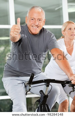 Happy senior man holding thumbs up on bike in fitness center - stock photo