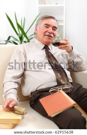 Happy senior man in living room with books, drinking coffee