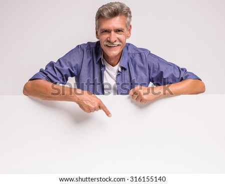 Happy senior man is holding blank placard on white background. Here can be your advertising. - stock photo
