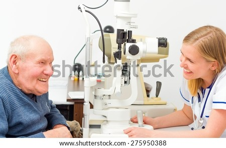 Happy senior man laughing with his doctor at the optical store. - stock photo