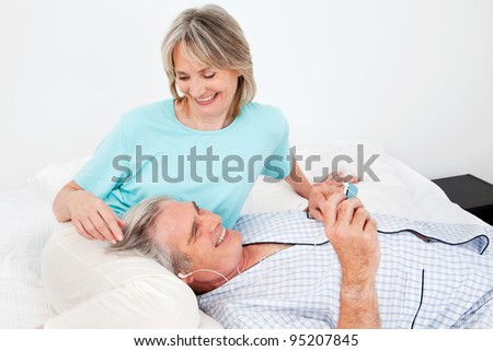 Happy senior man listening to music with headphones and small player