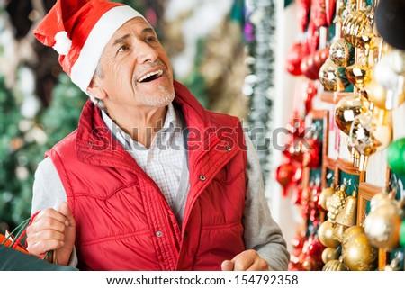 Happy senior man selecting Christmas ornaments at store - stock photo