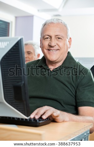 Happy Senior Man Sitting In Computer Classroom
