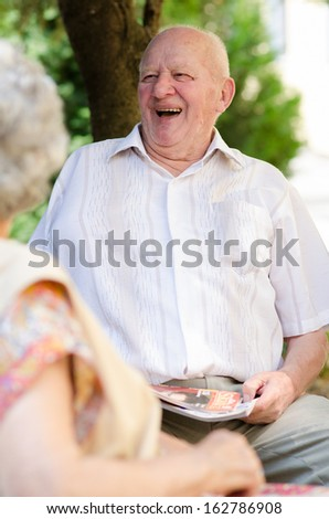 Happy senior man sitting outdoor and smiling - stock photo